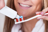 Mom put toothpaste on toothbrush — Stock Photo