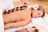Hot stones lined on her back — Stock Photo