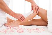 Esthéticienne, épilation à la cire une jambe de femme — Photo