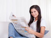 Woman sitting reading a newspaper — Stock Photo