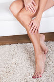 Woman stroking her bare legs — Stock Photo