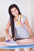 Cheerful housewife ironing the clothes — Stock Photo