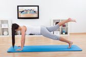 Woman practicing yoga at home — Stockfoto