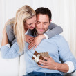 Woman giving her husband a surprise gift — Stock Photo #17391495