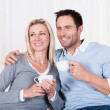Happy couple enjoying a cup of tea or coffee - Foto de Stock