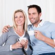Happy couple enjoying a cup of tea or coffee - Stockfoto