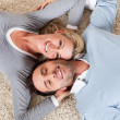 Man and woman lying head to head on the carpet - Stockfoto