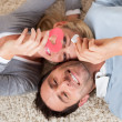 Stock Photo: Man and woman lying head to head on the carpet