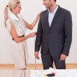 Seamstress measuring a man for a suit — Stock Photo #17392129