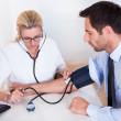 Stock Photo: Doctor taking patients blood pressure