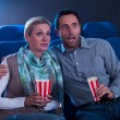 Couple watching movie reacting in horror — Stock Photo #17393127