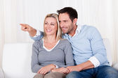Laughing couple pointing off screen — Stock Photo