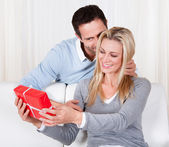Man giving his wife a surprise gift — Stock Photo