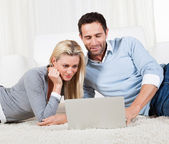 Couple lying on a carpet with a laptop — Stock Photo