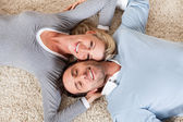 Man and woman lying head to head on the carpet — Stockfoto