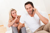 Man talking on his mobile watched by his wife — Stock Photo
