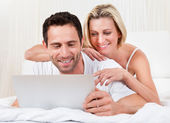 Young couple reading a laptop screen — Stock Photo