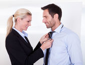 Businesswoman putting tie on businessman — Stock Photo