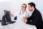 Doctor explaining something to a male patient — Stock Photo