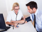 Doctor taking a patients blood pressure — Stock Photo