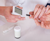 Doctor testing a patients glucose level — Stock Photo