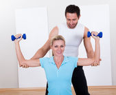 Fitness instructor helping a woman workout — Stock Photo