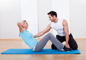 Fitness instructor teaching sit ups — Stock Photo