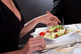 Man and woman holding hands over dinner — Stock Photo