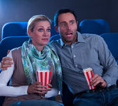 Couple watching a movie reacting in horror — Foto de Stock