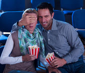 Couple watching a movie reacting in horror — Stock Photo