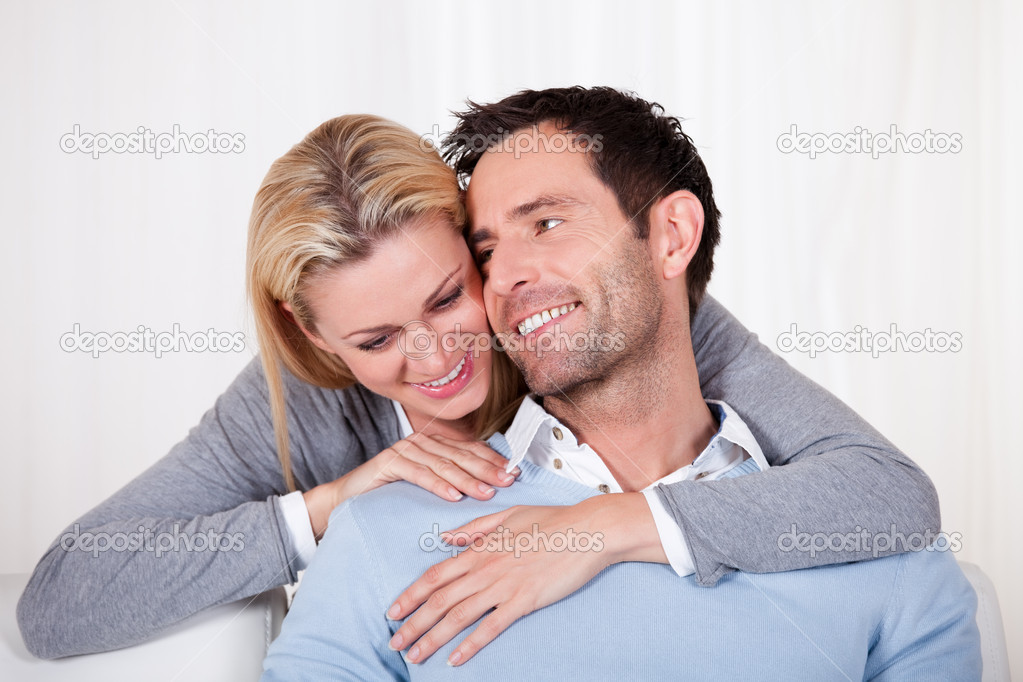 Affectionate couple relaxing on a sofa with the mans arm around his wifes shoulders as she rests her head on his shoulder — Stock Photo #17391475