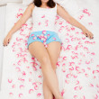 Rose petals surround a woman laying on a bed - Foto Stock