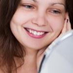 在她自己在镜子中微笑的女人 — 图库照片