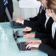 Businesspeople working on laptops and tablets - Stock Photo