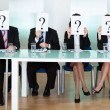 Row of businesspeople with question marks — Stock Photo #18597571