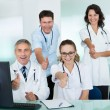 Happy medical team giving a thumbs up — Stock Photo