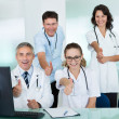 Happy medical team giving a thumbs up - Stock Photo