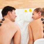 casal, desfrutando de uma massagem com pedras quentes — Foto Stock
