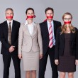 Businesspeople bound by red tape - Stock Photo