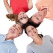 Four friends facing in with their heads together — Stock Photo