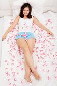 Rozenblaadjes omringen een vrouw tot op een bed — Stockfoto