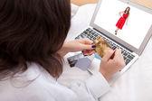 Woman purchasing a dress online — Stock Photo