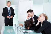 Bored businesswoman sleeping in a meeting — Stock Photo