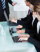 Businesspeople working on laptops and tablets — Stock Photo