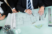 Architects discussing a blueprint — Stockfoto