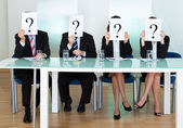 Row of businesspeople with question marks — Stock Photo