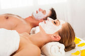 Muž a žena v pleťové masky — Stock fotografie