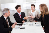 Businesspeople exchanging cards over coffee — Stock Photo
