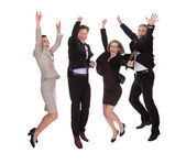 Four business partners jumping for joy — Stockfoto