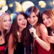 Four beautiful girls singing karaoke — Stock Photo